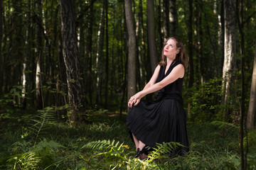 Delight in nature. Portrait of a young woman in a black dress sitting in the woods