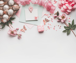 Modern styled Easter background with pastel color decoration: eggs, ribbon, flowers, bow and gift box. Mock up for Easter greeting card on white desk background, top view