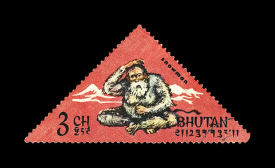 snowman (aka yetti) and mountains, circa 1966, vintage stamp printed in Bhutan isolated on black background
