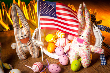 Easter in America. Rabbits keep the flag of the United States of America. . The Feast of Easter. Eggs and rabbits.