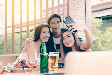 Group of asian smiling friends taking selfie in restaurant.