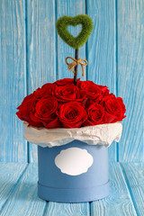 Red roses flowers in a blue box on turquoise wooden  background