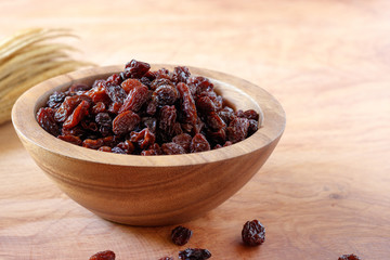 Raisin in bowl on wooden background.