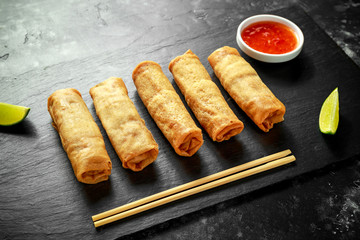 Chinese vegetable spring rolls with lime wedges, sweet chilli sauce.