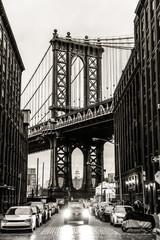 Manhattan Bridgeas seen from Washington street in Brooklyn, New York City, USA. Motion blured jogger running in foreground. Black and white image.