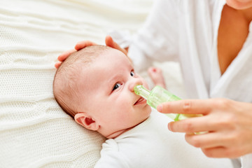 Nase von Säugling wird von Schleim befreit