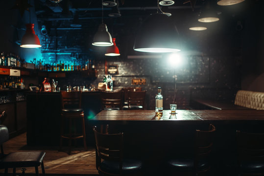 Pub, bottle of alcohol and glass on bar counter