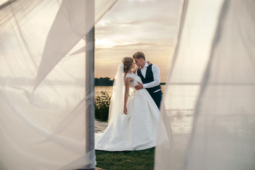 The bride and groom in wedding dresses on natural background. Newlyweds are walking along the river bank at sunset.