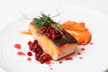 Fried salmon steak with pumpkin puree, berry sauce and herbs