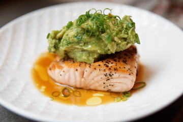 Grilled salmon fillet with guacamole and crushed nuts