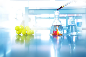 orange drop solution into water in glass flask with chemical yellow structure in science laboratory background