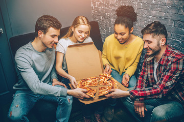 Group picture of students where everybody is holding a peace of pizza. They are so hungry that they can't wait anymore and want to eat it right now. Party night