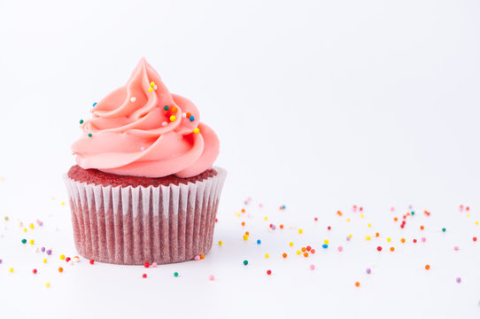 Cupcake red velvet with blue and pink whipped cream decorated with colorful sprinkles on white background.