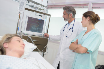 female patient in bed while doctors looking at x-ray