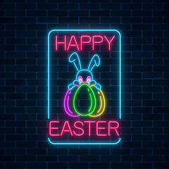 Glowing neon sign of easter bunny with eggs rectangle frame with greeting inscription on dark brick wall background.