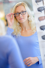 girl trying on glasses with black rims