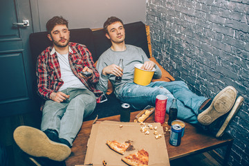 Two guys sitting on the couch and holding some food and drinks in their hands. They feel relaxed and tired after a long match playing different games. Now young men want to have some rest