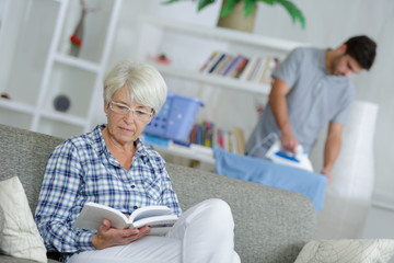 woman sitting on sofa with book while male carer standing