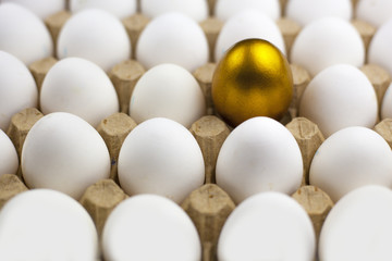 Chicken egg with a gold pattern surrounded by white eggs, background, texture.
