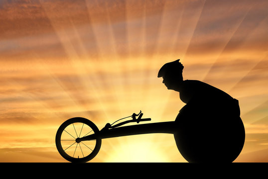 Silhouette of sportsman disabled in a racing wheelchair