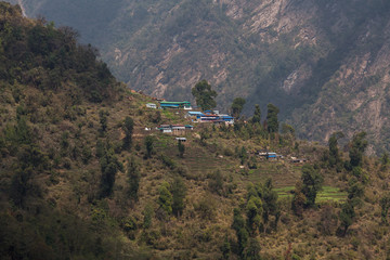 The mountain village in Nepal located on cascades and surrounded by greenery.