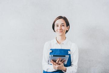 タブレットPCを持つエプロンを着た女性