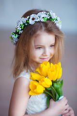 Beautiful little girl with a bouquet of tulips. Spring and summer portrait of cute child holding flowers.