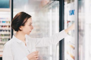 店舗の冷蔵庫から飲み物を選ぶ女性
