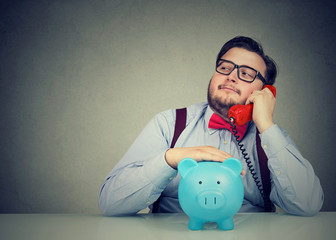 financial advisor with piggy bank callling on the phone