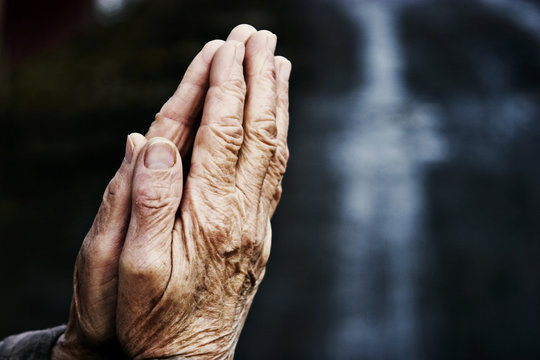 Hands of an old grandmother in prayer on a dark background