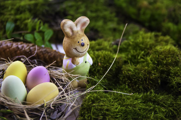 Easter holiday concept with cute handmade eggs, bunny, chicks and party hats in bowl on wooden table