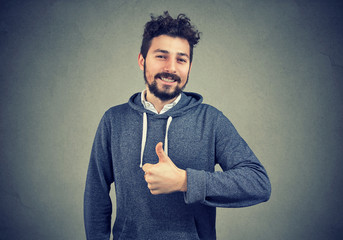 Content successful hipster gesturing on gray