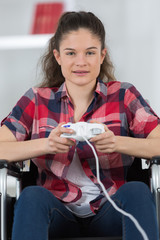 young happy disabled woman playing video games at home
