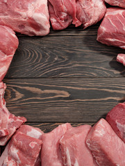 Assorted raw meat on a wooden dark background. Mock-up