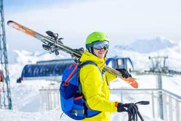 Photo of sporty man wearing helmet with skis on his shoulder against backdrop of funicular
