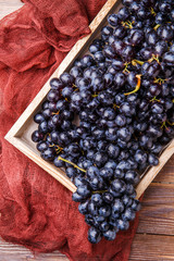 Photo of black grapes in wooden box with claret cloth