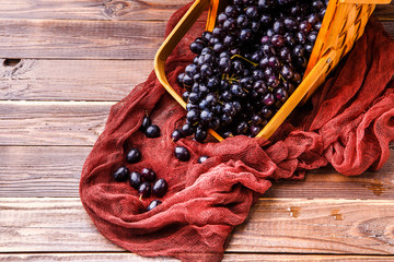 Image from above of black grapes in wooden basket with claret cloth