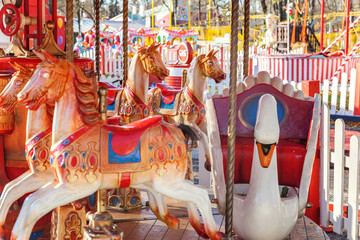Outdoor colourful vintage flying horse carousel in the park