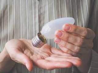 Broken light bulb in his hands. A marriage work.