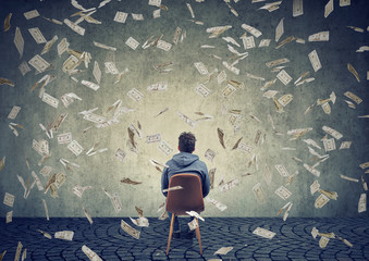 man sitting on chair in front of a wall under money rain