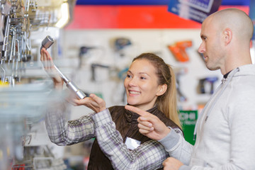 female hardwarer store worker assisting male customer