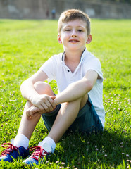 boy in shirt sitting on the grass