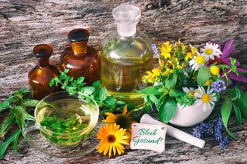 Kräutertee mit Medizinflaschen und heilenden Kräutern im Mörser. Bleib gesund