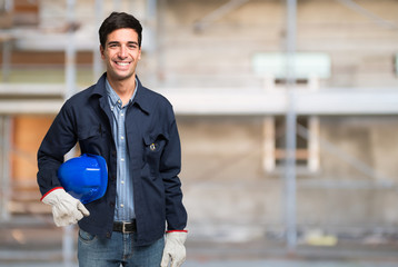 Smiling worker in front of a construction site