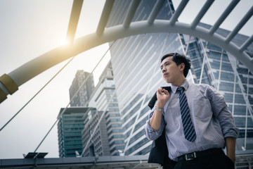 Asian businessman standing outdoors with office building in the background, low angle view