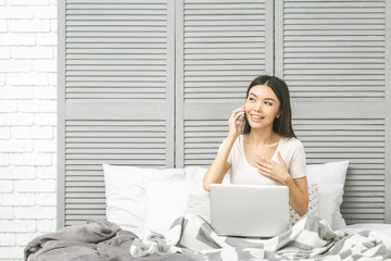 Happy casual beautiful woman working on a laptop sitting on the bed in the house. Working at home. Freelance concept.