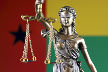 Symbol of law and justice with Guinea Bissau Flag. Close up.