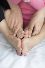 Baby feet in mother hands. Close up of little baby feet in hands of mother.Selective focus