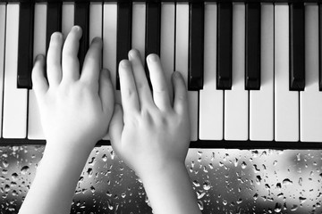 A photo of an adult and a child's hand on a piano keyboard, drops on a glass