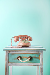Pink retro telephone on wooden nightstand